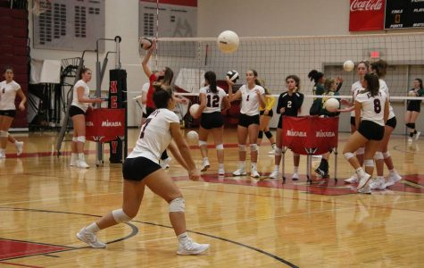 Junior Isabella Miller goes up to bump the ball during warmup.