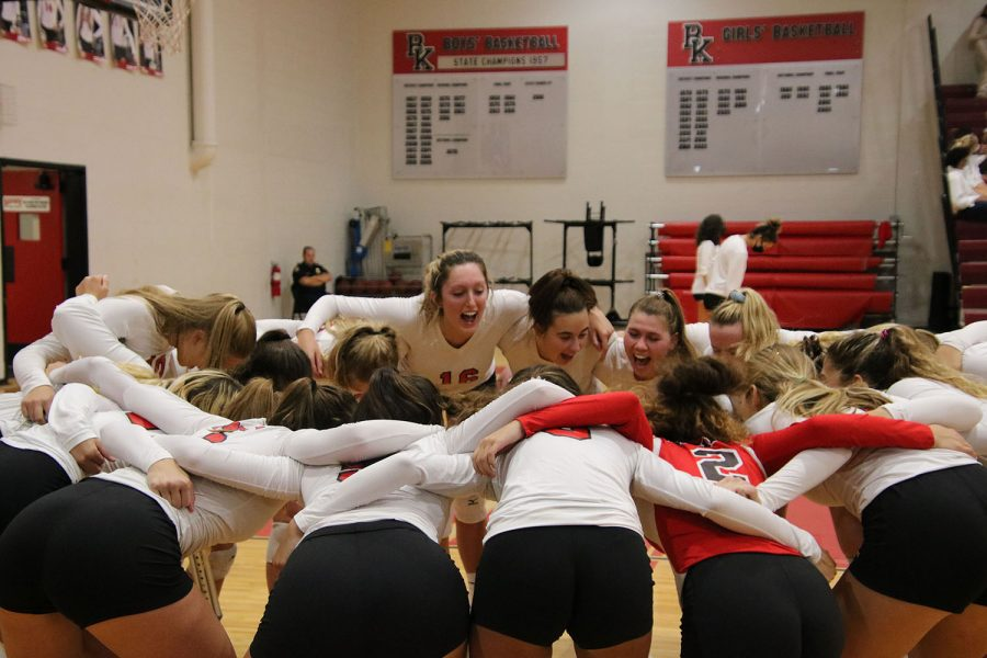 In a pre-game huddle, the Varsity team yells with joy.