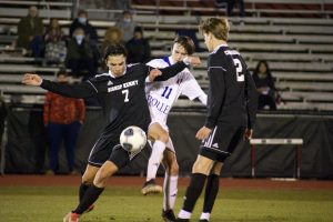 Junior Raf Montalvo in a play against opposing team, passing to senior Lucas Sams