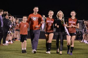 Senior Chloe Shaw walking down the field with her family and sister, sophmore Stella Shaw.