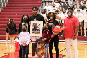 Senior Kenny Patterson,  number four, poses with his family for senior night.