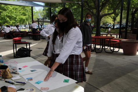 Seniors Sarah Ward and Mary Jackson Kirk pick up trading cards made by members of the art club.